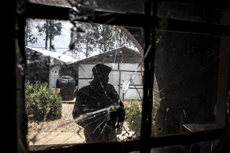 Photo d'un policier derrière un impact de balle après une attaque visant un centre médical où sont soignés des patients Ebola.