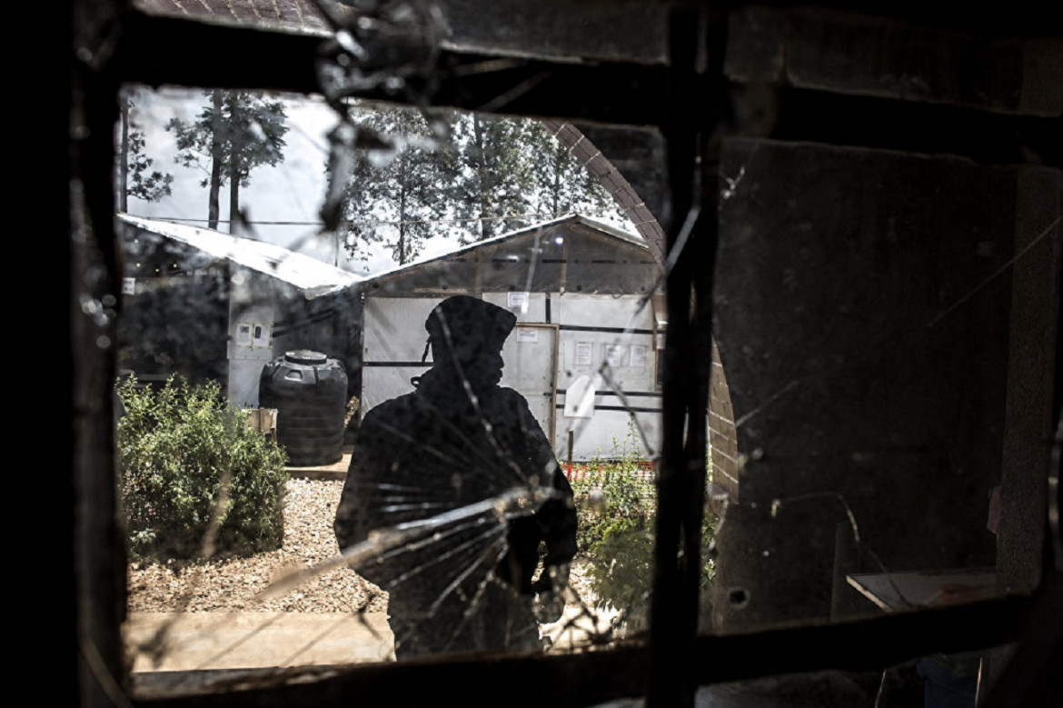 A photo of a police officer taken through a bullet hole left after an attack on a clinic where patients with Ebola are being treated.