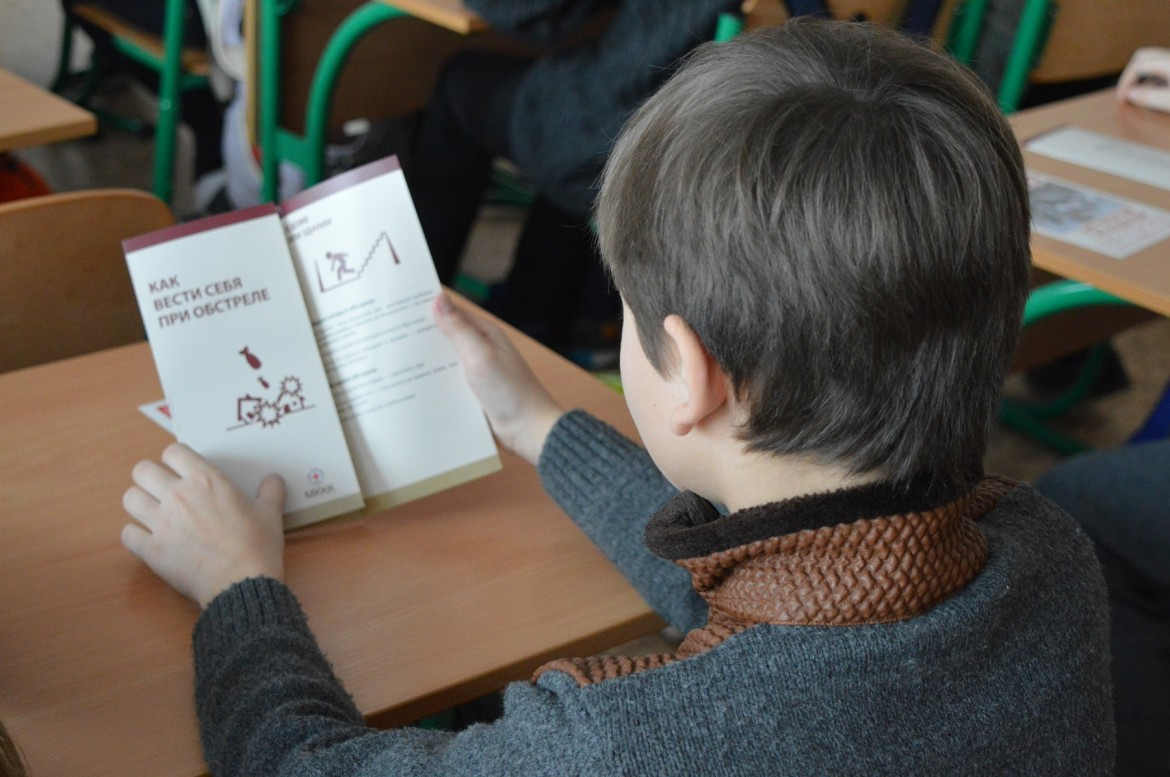 A school boy reading what to do in case of shelling, February 2018