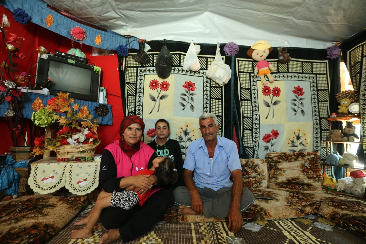 Abu Khaled sits with his family in their tent on the edge of Ras Baalbek, Lebanon, July 2015.