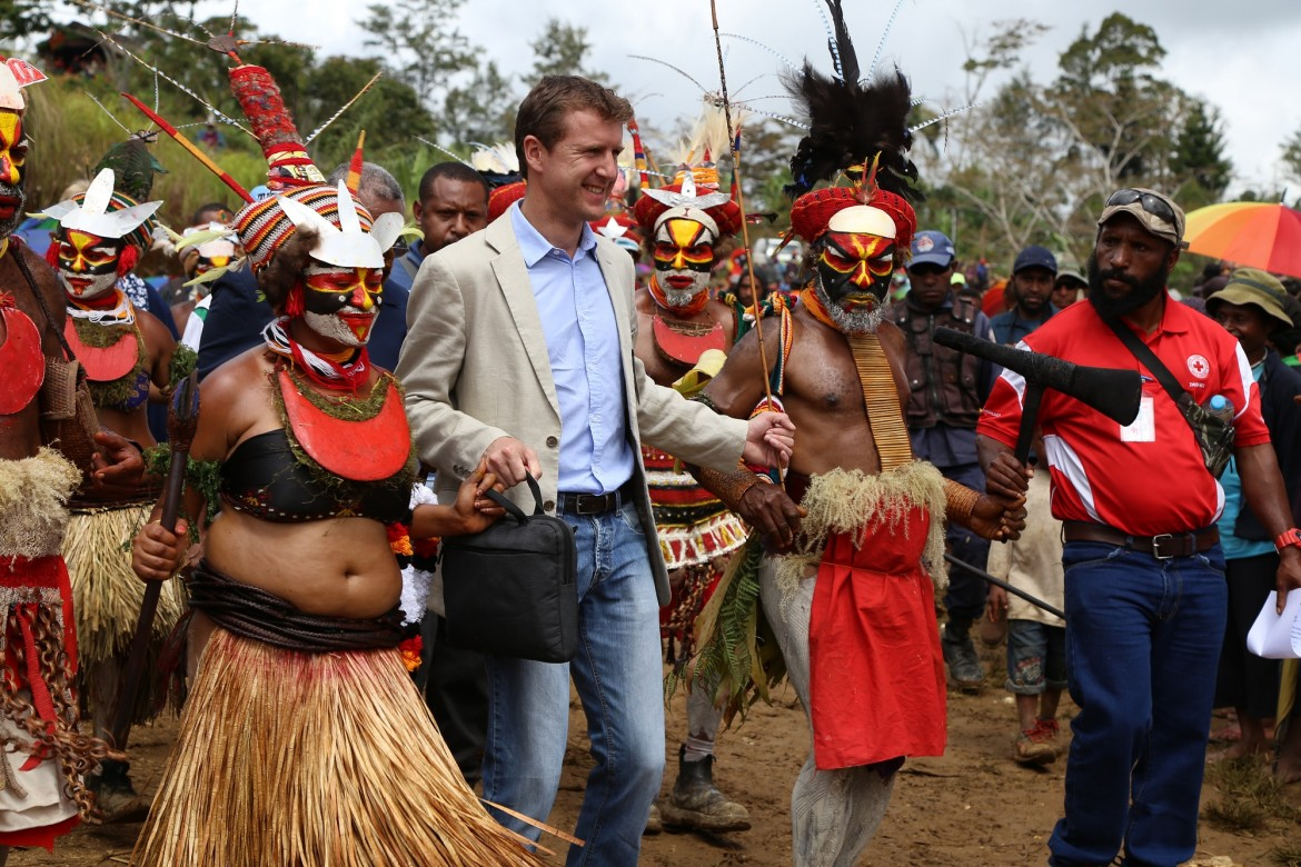 ICRC Mt Hagen Acting Head of Office Thomas Rogale (centre) is escorted into the village in traditional style.
