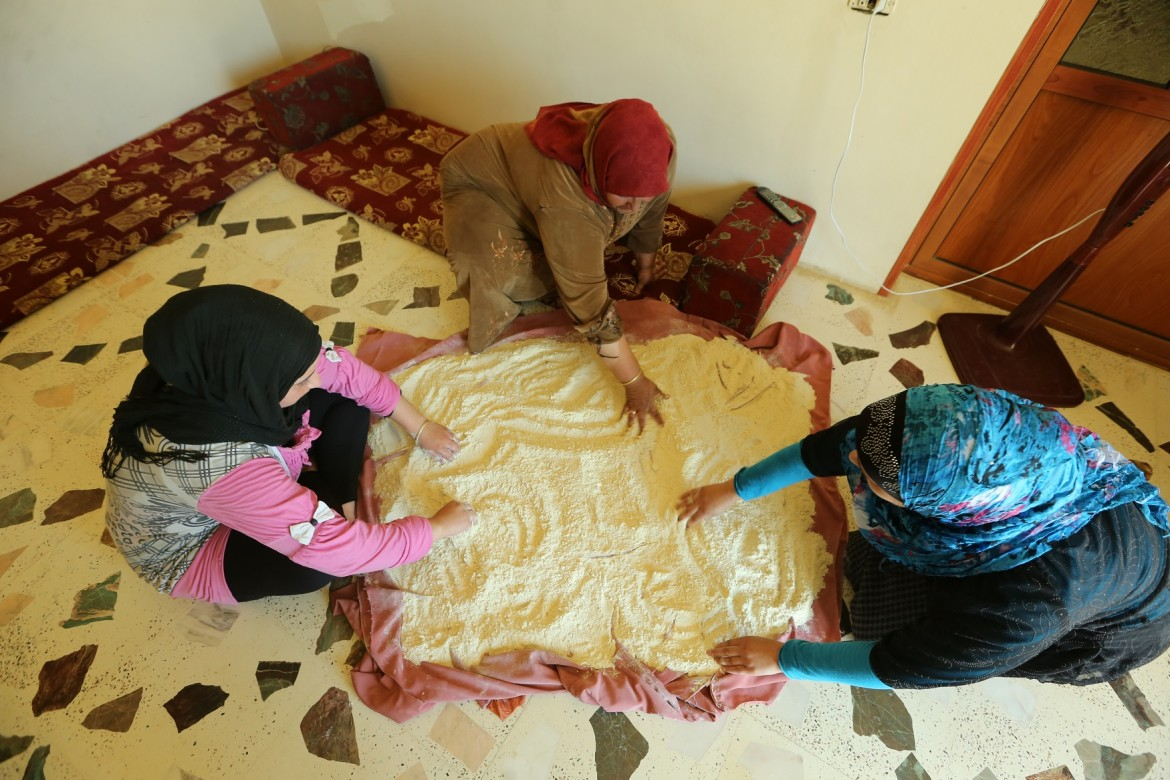 Um Mohammad prepares Kishik with her two daughters. Ras Baalbek, Lebanon, July 2015.
