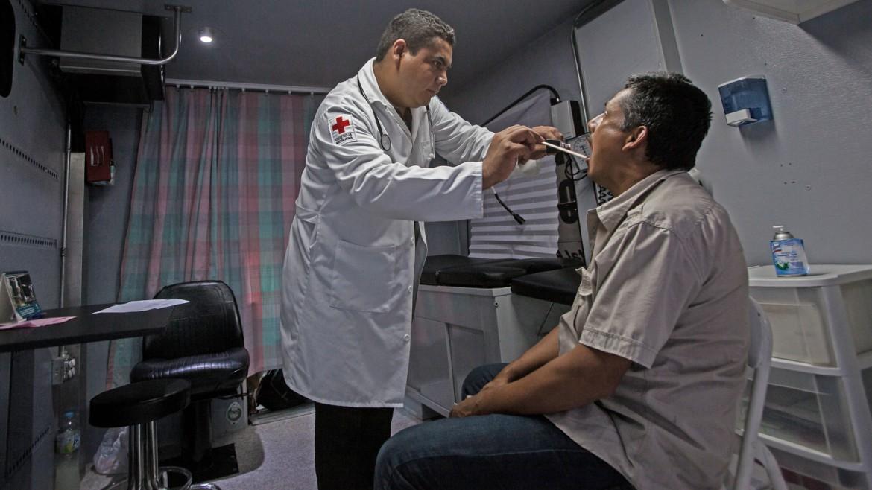 2014年9月,墨西哥,蒂华纳。墨西哥红十字会志愿者在流动诊所为移民提供医疗服务。