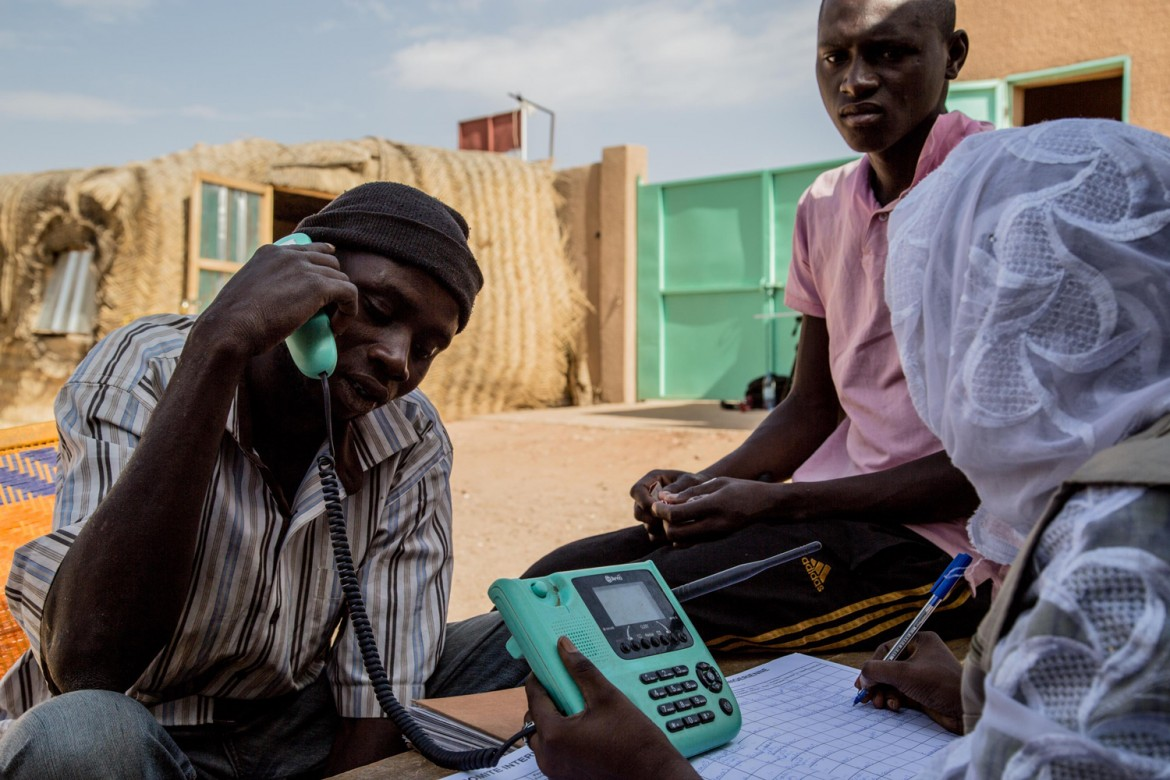 Agadez, Niger, 31 March 2014. A volunteer from the Niger Red Cross helps a migrant contact his family via a free phone call.