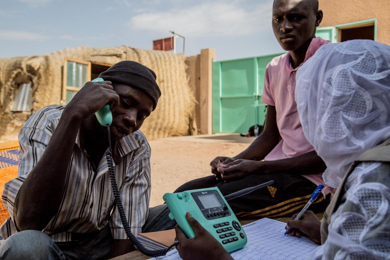Agadez, Niger, 31 mars 2014. Une volontaire de la Croix-Rouge nigérienne aide un migrant à contacter gratuitement sa famille par téléphone.
