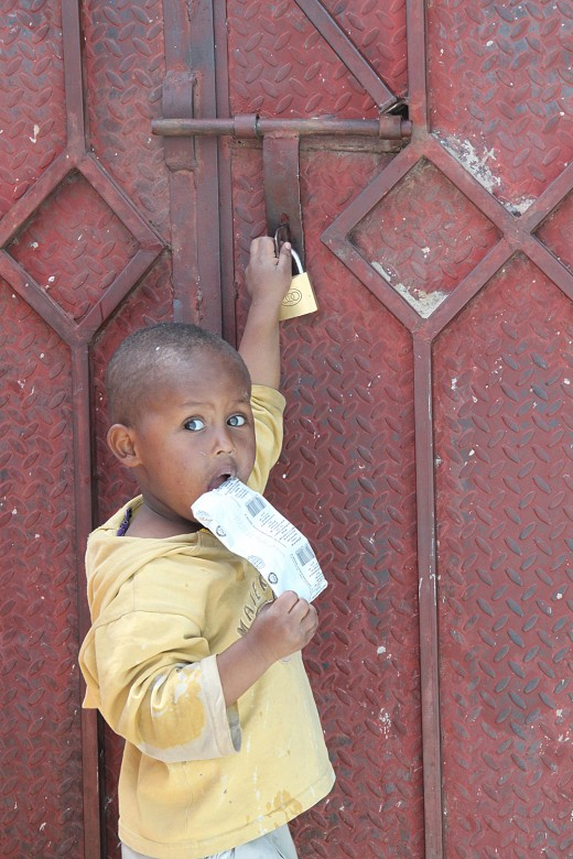 也门,萨那,护照事务处。一个小孩站在他妈妈的牢房外。