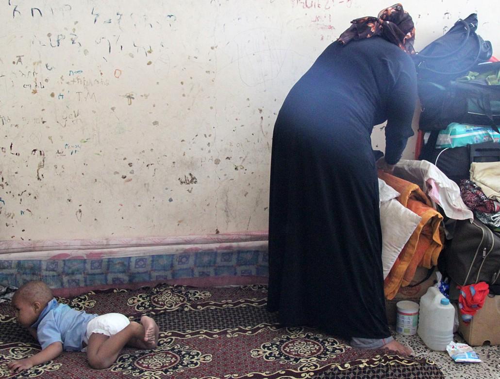 也门,萨那,护照事务处。一名埃塞俄比亚妇女和她的孩子等待遣返。