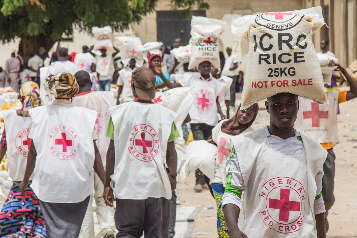 Volunteers of the Nigerian Red Cross and the ICRC distribute food items to internally displaced families in Maiduguri, Borno State.