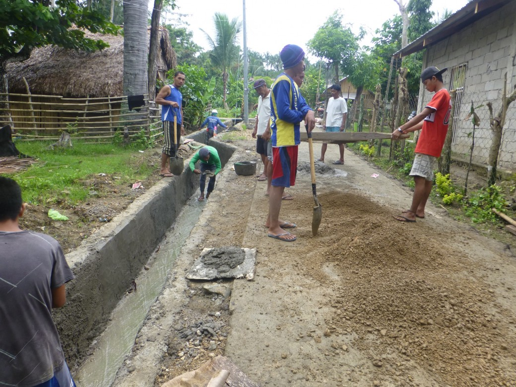 Workers are selected by a committee composed of five members  including representatives from the Barangay Local Government Unit (BLGU), farmers' association, women's association, Barangay health workers, religious leaders, etc. Photo: Workers improve the drainage canal to reduce flooding in Barangay Cantorna, Monreal, Masbate. Photo by by ICRC/J. Angolluan
