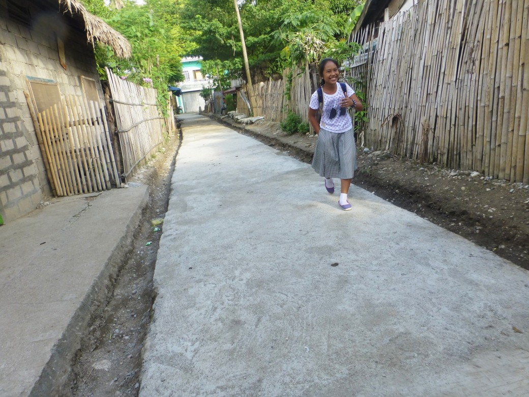 A young girl walks on a newly-improved concrete road in Barangay Togoron, Monreal in Masbate. Photo by ICRC/J. Angolluan
