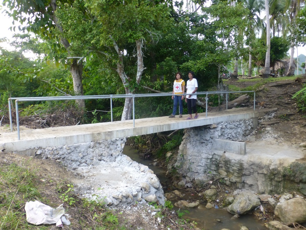 "Resident Adelfa Delos Santos, 67, of Barangay Sto Niňo, Monreal, Masbate narrated: ""I have been here since in 1963 and this bridge is a dream come true. It is very useful and very safe for those who are crossing the creek which can be very dangerous during flooding."" Photo by ICRC/J. Angolluan"