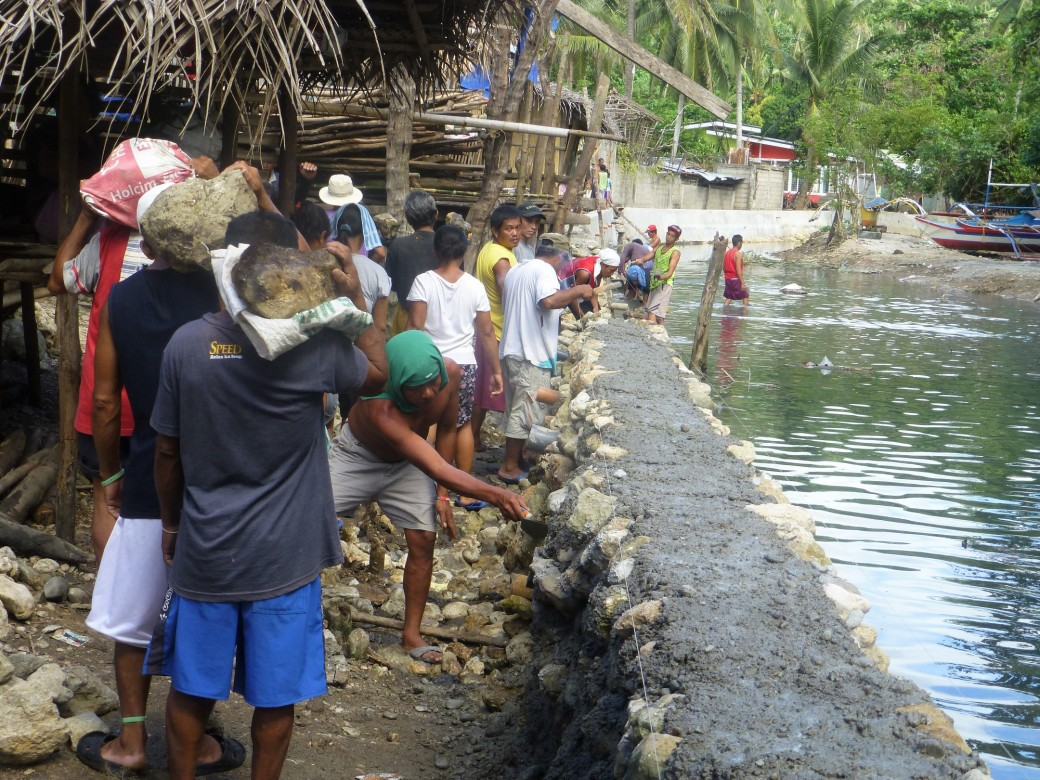 In Barangay Togoron, Monreal in Masbate, workers construct a river wall to prevent flash floods and erosion from damaging houses. Photo by ICRC/J. Angolluan