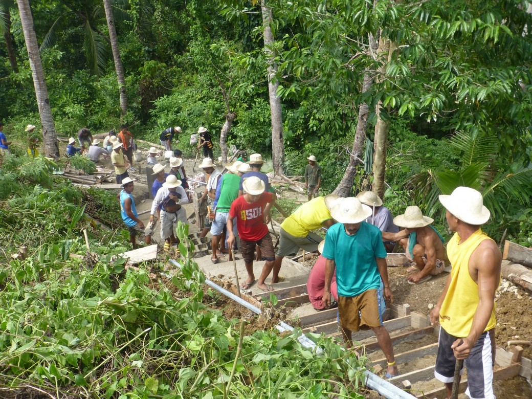 In Barangay Bartolabac, San Jacinto, workers construct a staircase that leads to a water point. Before the construction, villagers would struggle walking up the steep and muddy hill especially during heavy rain. Photo by ICRC/J. Angolluan