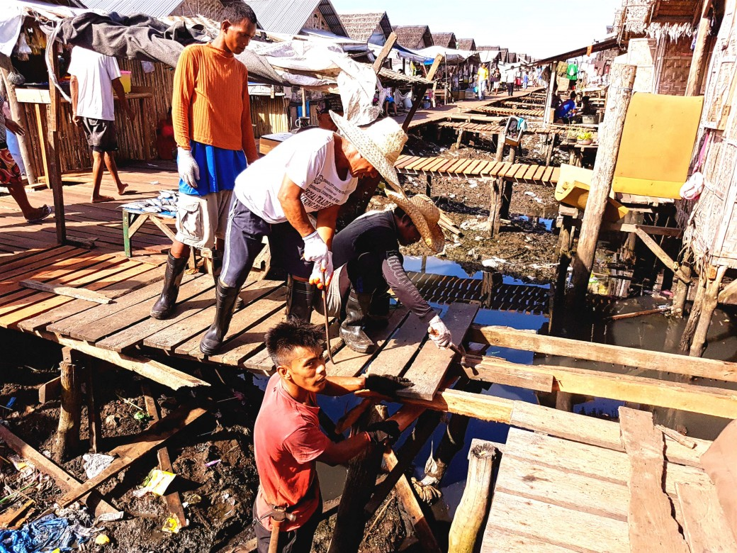 In Masepla, the workers take their time to align and carefully fit the custom-cut wooden planks for the boardwalk. A total 178 displaced people joined the cash-for-work project implemented in Masepla and Buggoc transitory sites.  Photo by: Arben Balsote