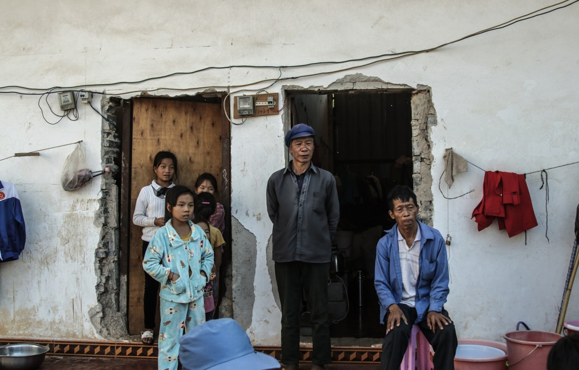 Locals of Laukkhaing community look on as their family members and neighbours collect blankets and mattresses.