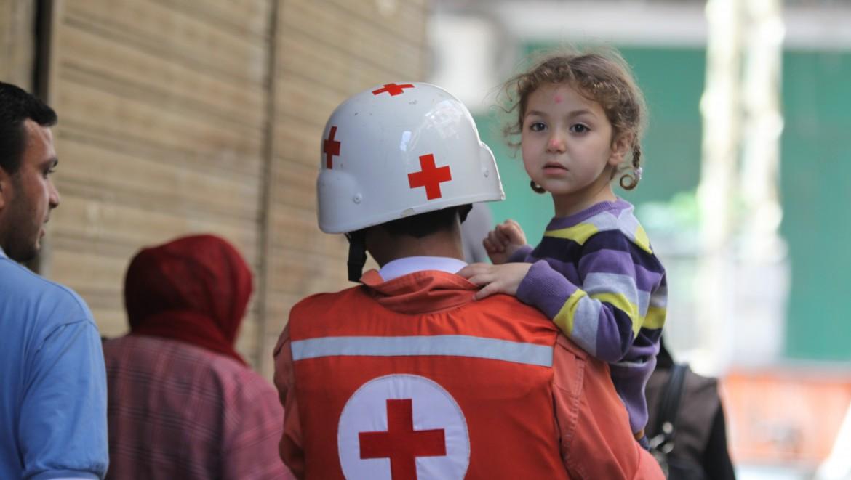 2012年。在黎巴嫩北部城市的黎波里遭受连番暴力袭击期间,黎巴嫩红十字会志愿者帮助一名小女孩撤离。
