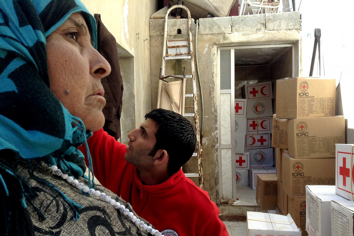 A woman waits for a Red Cross food parcel in Rural Aleppo after fleeing her home in Raqqa.