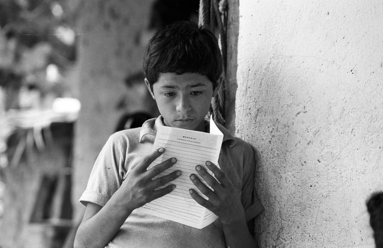 Joven recibe noticias de un ser querido con quien ha perdido contacto, a través de un Mensaje Cruz Roja durante el conflicto armado.