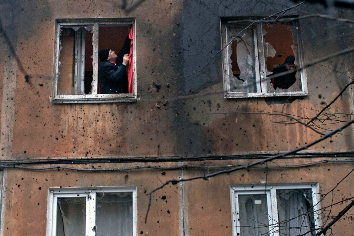 Donetsk, Ukraine, January 2015. A man tries to repair a shell-damaged window in his apartment.