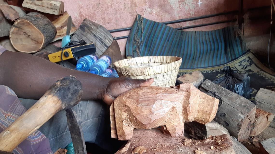 Barou* sculptant le bois pour lui donner la forme d'un hippopotame. CICR