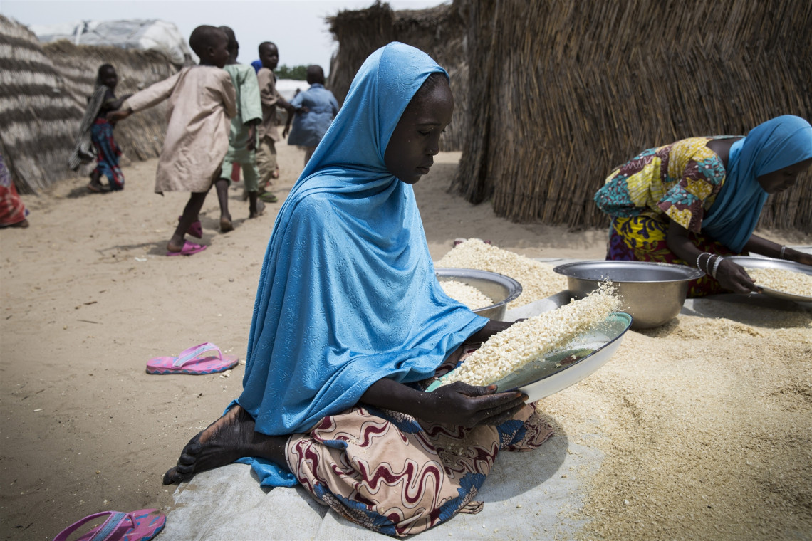 Borno State, Nigeria. A woman sifts maize in a camp where people have sought refuge from fighting, September 2019. C.A. Wells / ICRC