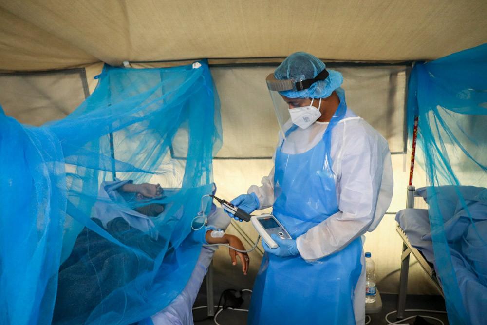 Un doctor y un paciente en un centro de atención por COVID-19 en Aden, Yemen.