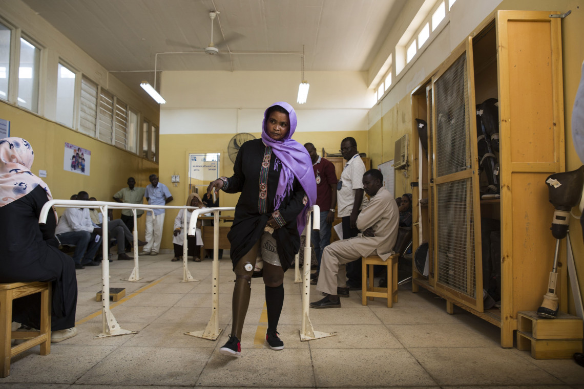Khartoum, National Authority for Prosthetics and Orthotics (NAPO). Mahaussan Hamed Habeeballah walks with her new prosthetic leg. It is the first time she has had a new prosthetic fitted in 11 years. Crystal Wells / ICRC