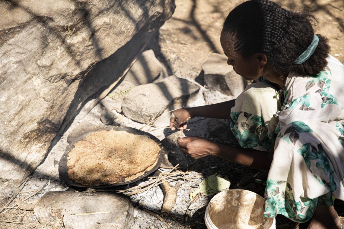 Región de Tigray, Axum. Una mujer desplazada por los enfrentamientos prepara una comida. CICR / Alyona Synenko
