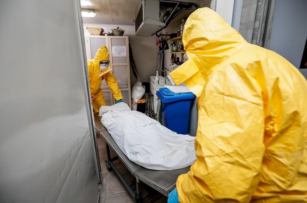 Angestellte holen die Leiche eines COVID-19-Opfers im doppelten Sack aus einem Kühlraum. Stephanie Lecocq / EPA