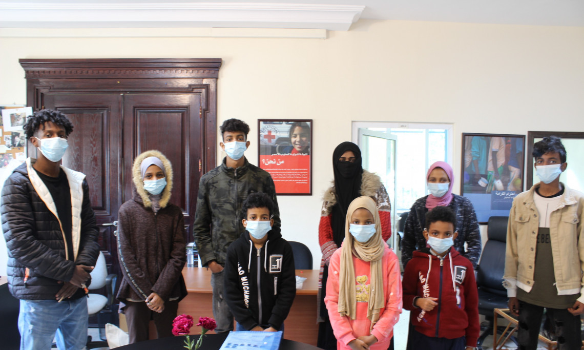 Hasan, standing on the left, with his mother and 6 siblings at the ICRC office in Jordan