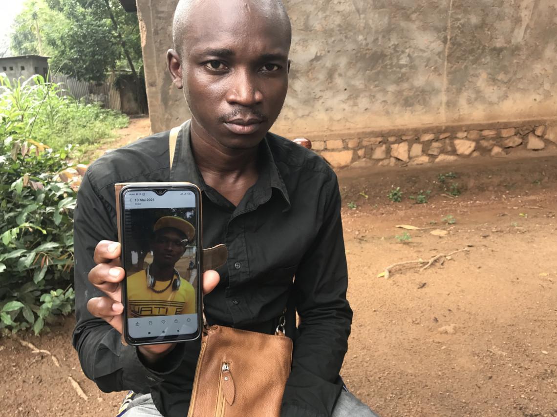 Le frère ainé du disparu J.M.T.K, montre la photo de son petit frère disparu.