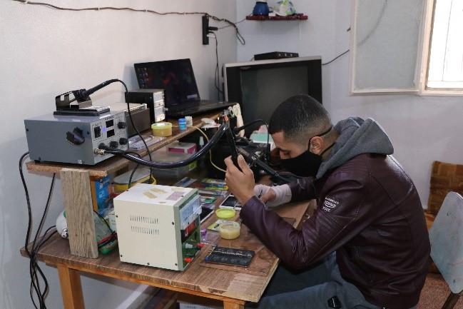 محمد أثناء قيامه بعمله حيث يقوم بإصلاح أحد الهواتف. تصوير: رفاه الحديدي - اللجنة الدولية