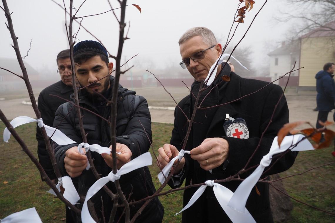 Магне Барт повязывает белую ленточку в память о погибших в Новых Атагах, декабрь 2018 г. (c) ICRC / Galina Balzamova