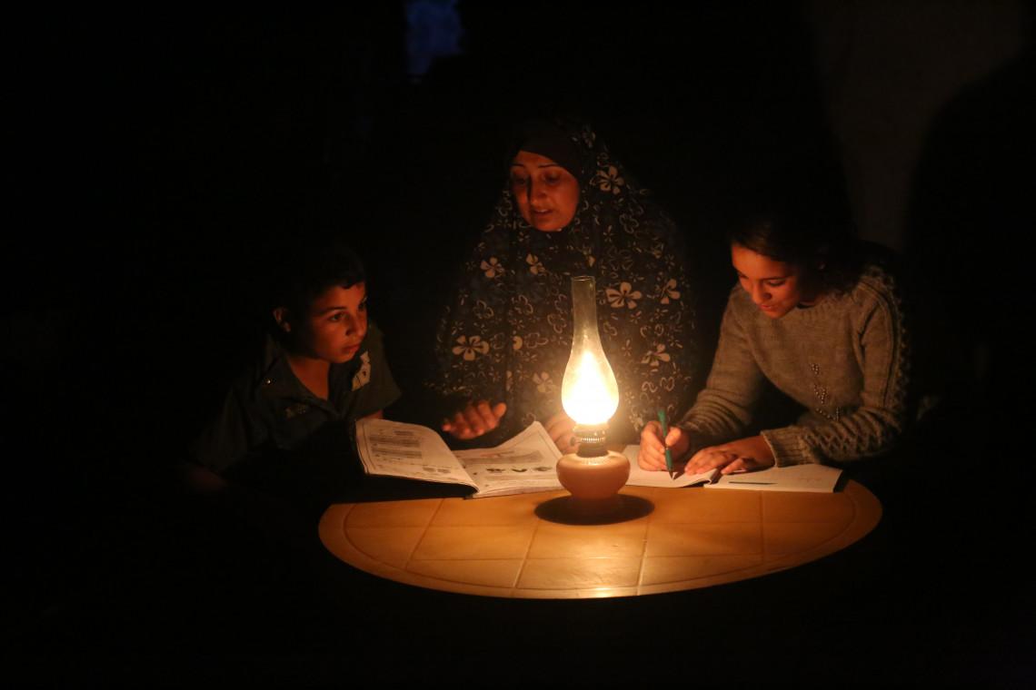 Família em Gaza estuda no escuro