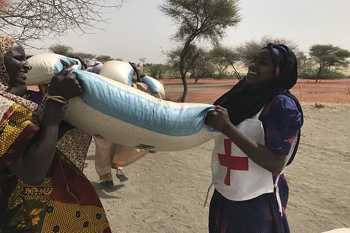 Une volontaire aide une bénéficiaire lors d'une distribution à Kishira.