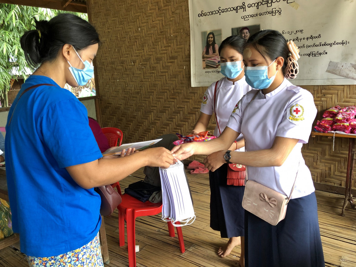 Volunteers distribute fabric masks to community members after production by displaced people in Kachin. May Myat Noe Aye / ICRC