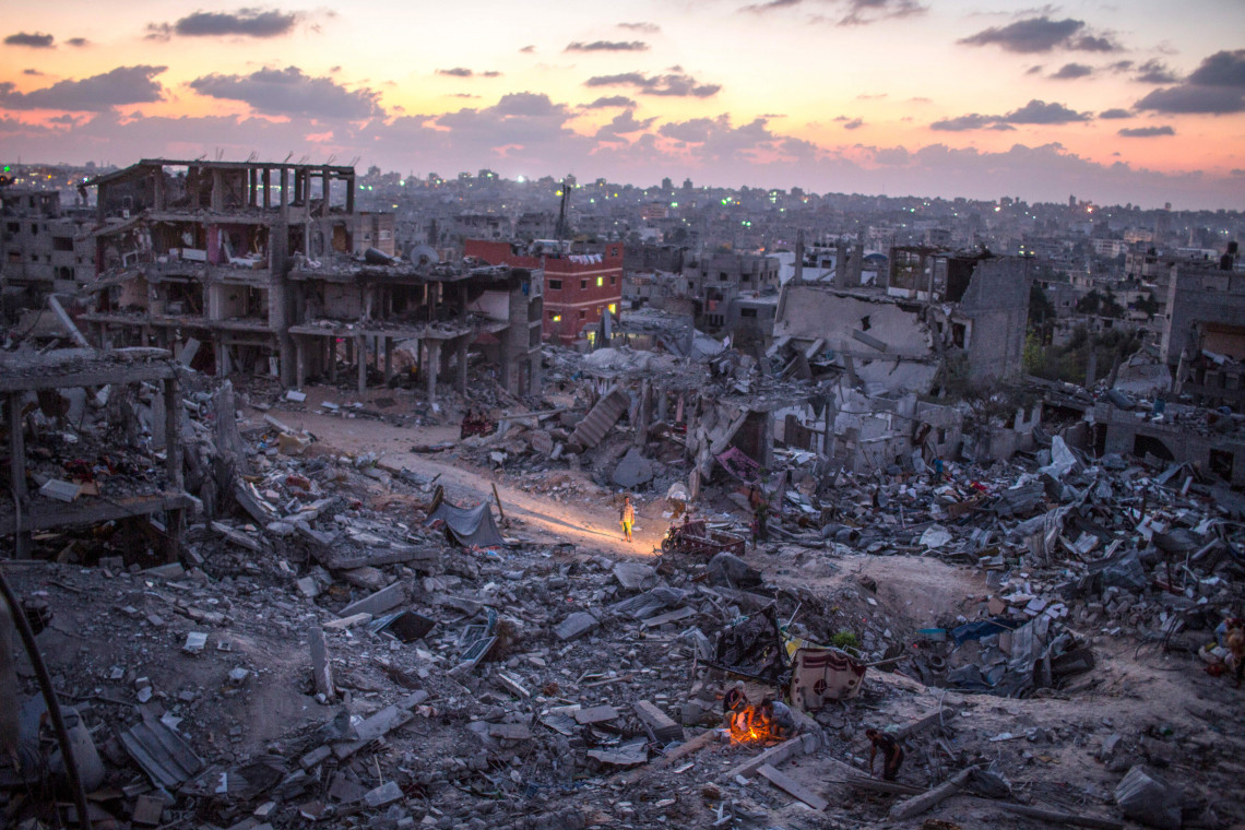 Residents of the Sha'af neighborhood of Gaza light a fire at sundown in the rubble of their destroyed neighborhood on August 28, 2014. Wissam Nassar/The New York Times