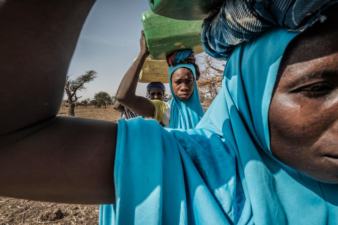 Village de Sera. Badigueta Barry (au centre), éleveuse de 34 ans, est mère de 4 enfants. Elle a fui la ville de Barsalogho il y a un an avec son mari, en laissant tous ses biens derrière elle. Elle va chercher de l'eau à l'unique puits qui se situe à plus d'un kilomètre du village, en compagnie de deux autres femmes.