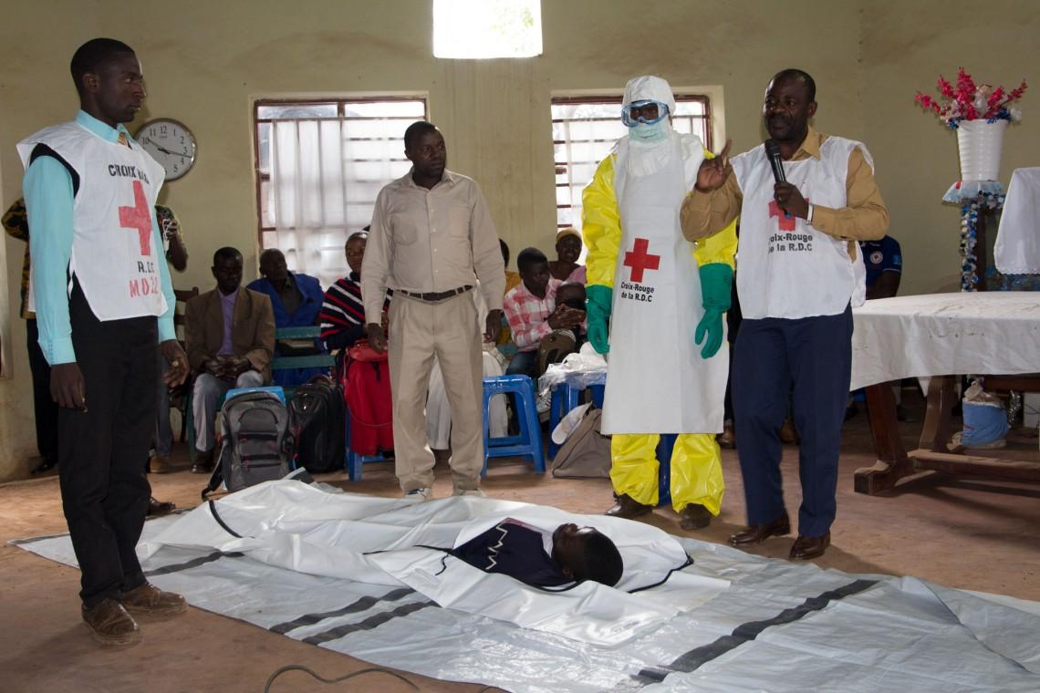 Au cours des séances de sensibilisation organisées à l'intention des membres des communautés, les volontaires de la Croix-Rouge expliquent le comment et le pourquoi de l'utilisation de sacs mortuaires pour les inhumations sans risque et dans la dignité.