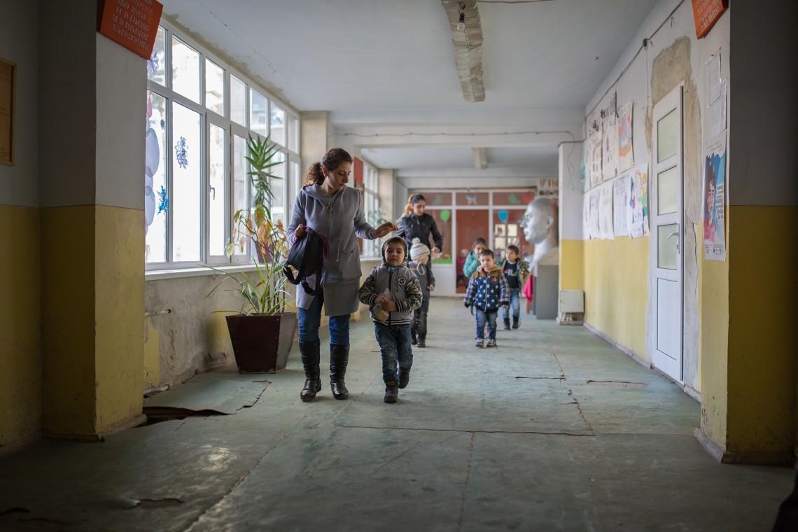 Des enfants d'âge préscolaire avec leurs parents dans le couloir de l'école de Khndzorut. CC BY-NC-ND / CICR / Areg Balayan