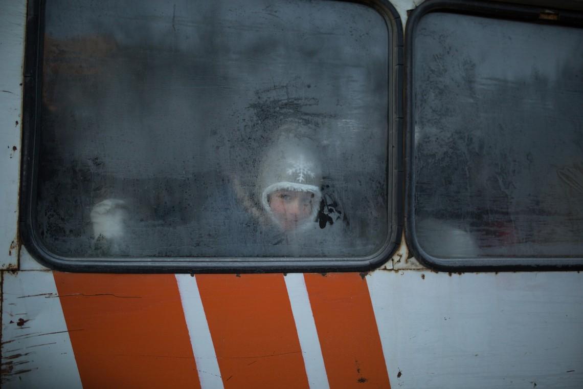 Tôt le matin, un enfant r egarde à travers la fenêtre gelée du bus qui le conduit à l'école.CC BY-NC-ND / CICR / Areg Balayan