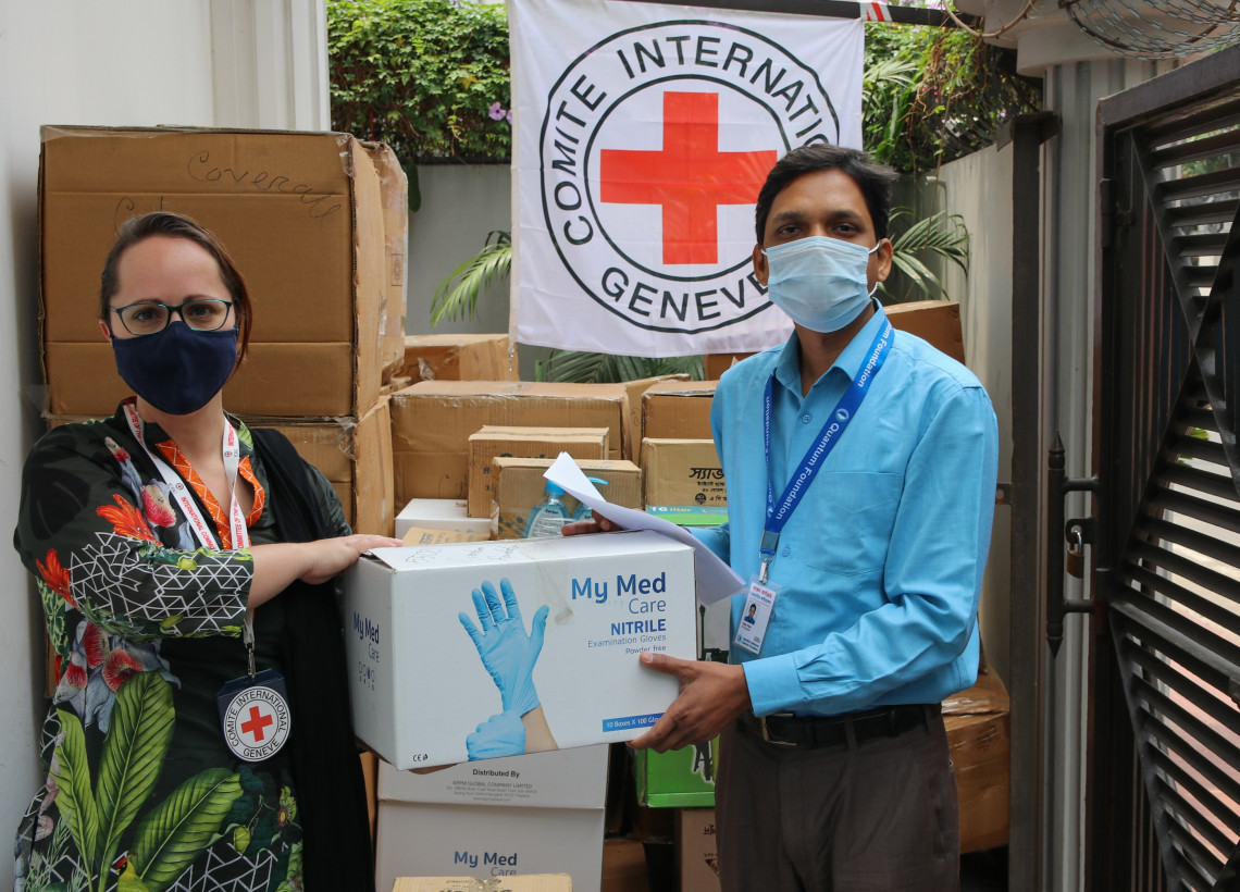 A representative of Quantum Foundation, which has been working relentlessly to ensure proper burial for COVID-19 deceased, receives body bags and PPE from the ICRC. © S.Hossain /ICRC