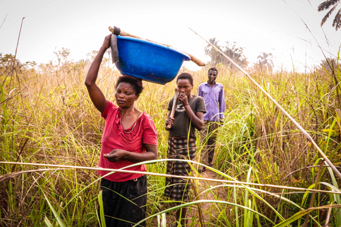 Marie, her husband and daughter walk to the field they are farming together.