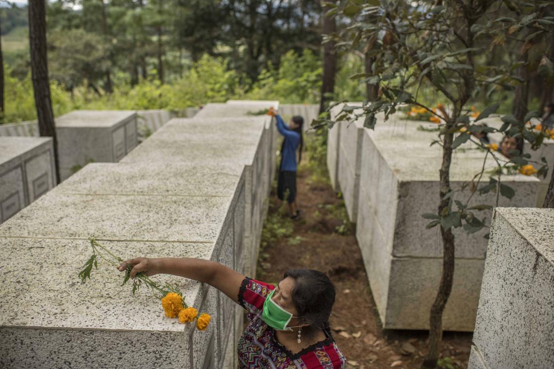 Rosalina Tuyuc, de 64 años de edad, y sus familiares decoran las tumbas donde descansan los cuerpos de 220 víctimas del conflicto armado, que fueron hallados por antropólogos forenses. Durante la guerra civil, el ejército reclutó al padre y al marido de Rosalina. Hasta hoy, ella y su familia siguen sin conocer el paradero de sus seres queridos y continúan buscando sus cuerpos.