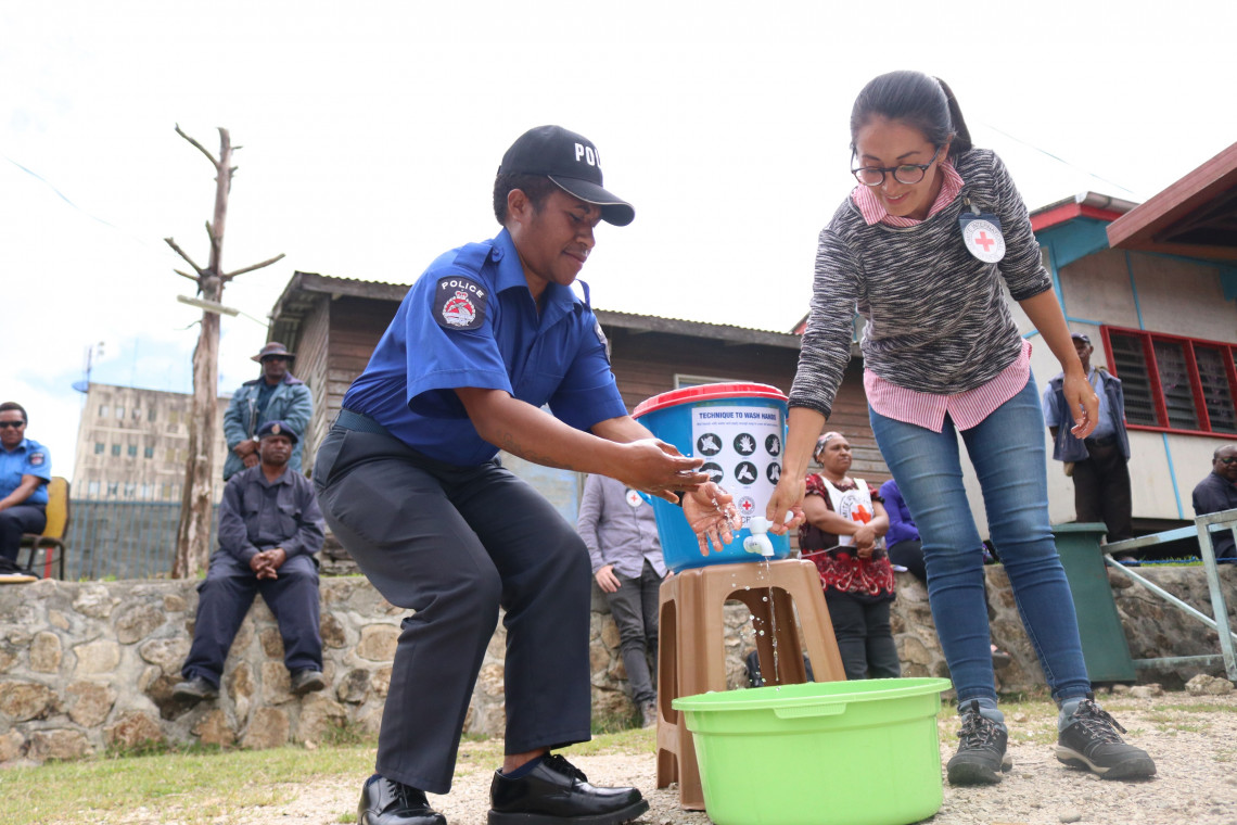 A PNG constable demonstrating handwashing techniques alongside an ICRC delegate during COVID-19 awareness-raising session with police in Mendi.