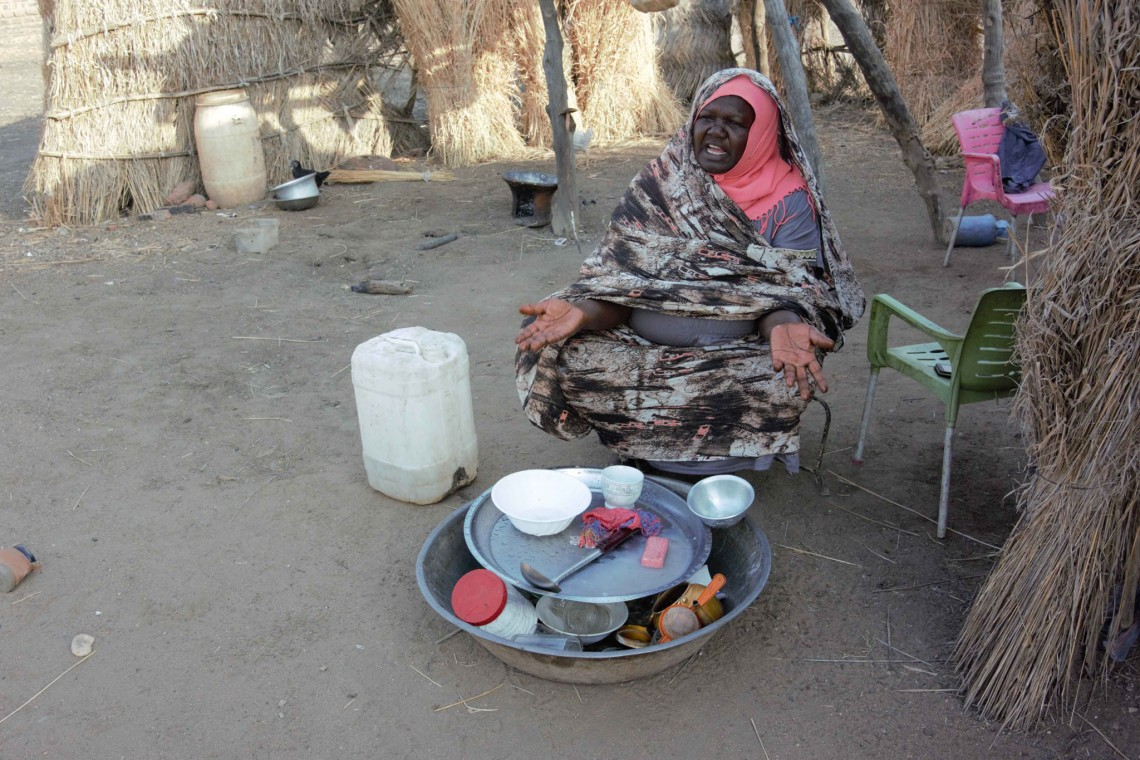 Suad washes the dishes in her family's compound with water from a jerrycan. Photo: Jessica Barry / ICRC