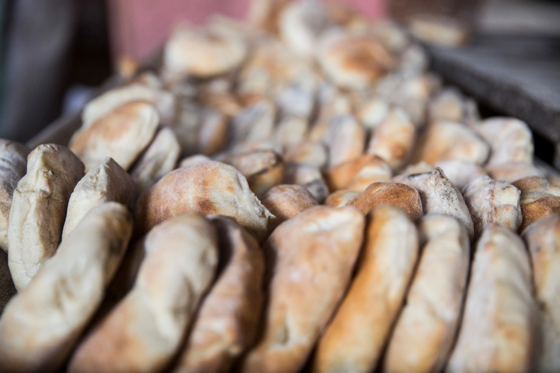Freshly baked Sudanese bread on the outskirts of Khartoum   where Faris works. He is on his feet nearly all day, mixing, kneading, and rolling dough. When he finishes work, he dashes off to workshops and classes around town. Photo: Crystal Wells / ICRC