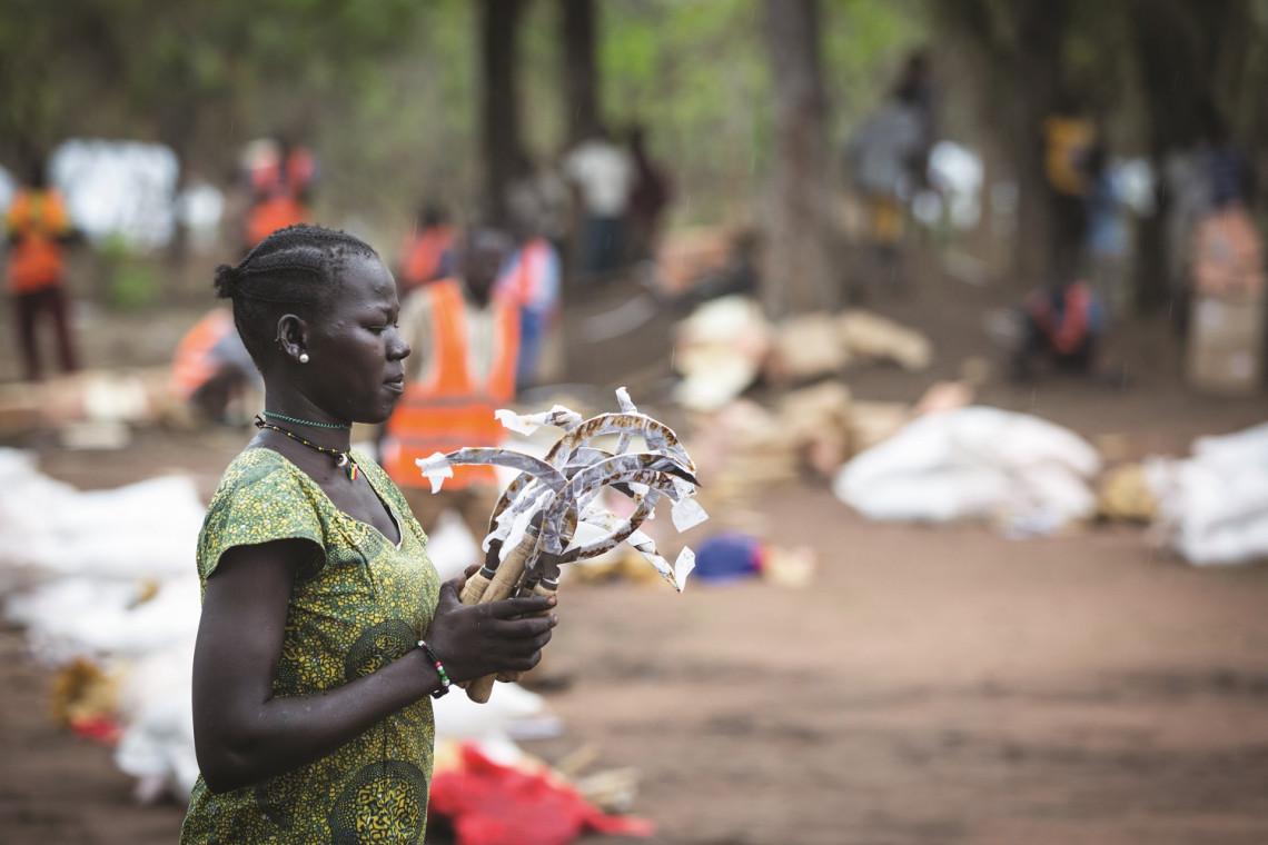 Uma mulher carrega um conjunto de ferramentas agrícolas que serão compartilhadas com outras famílias. 2019, Dulamaya, Sudão do Sul.