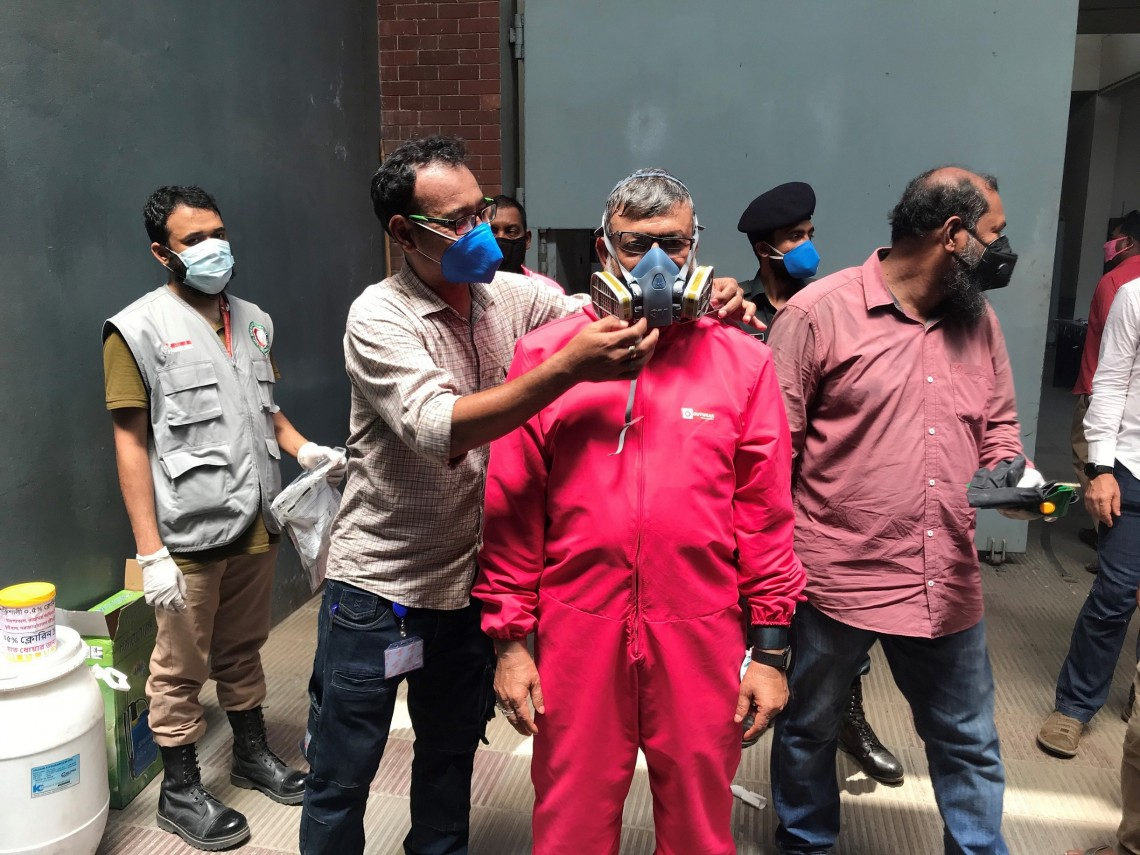 ICRC engineer helps a prison staff wear the special protective mask during the chlorine mixing exercise. R.Sircar/ICRC