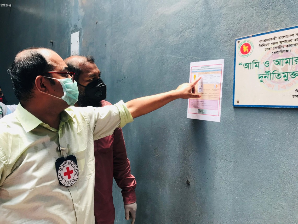 An ICRC engineer shows a prison staff the instruction poster on how to prepare Chlorine solution, pasted on the entrance wall. R.Sircar/ICRC